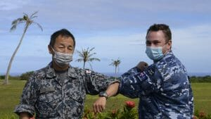 """Image of Chaplain Stuart Asquith from RAAF Base Townsville shares a """"COVID-safe elbow tap"""" with Japan Air Self-Defense Force senior enlisted member, Warrant Officer Yoshiaki Tanide at Andersen Air Force Base in Guam during Exercise Cope North 2021."""