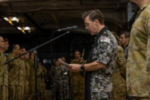 Image of HMAS Canberra Chaplain Darren Hindle reads the opening prayer during a ceremony held on board Royal Australian Navy ship HMAS Canberra to commemorate the Blackhawk Accident of 12th June 1996.