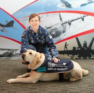 Image of Hooper, the Workplace Welfare Dog, receives a pat from Chaplain Emma Street during Hooper's visit to Air Force 2021 at RAAF Base Fairbairn, ACT.