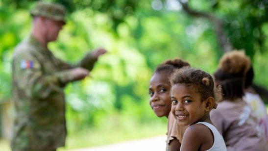 Image of Local children (L-R), Jesmina and Velona, watch on as Australian Defence Force personnel conduct Phase 2 of the Vanuatu Government National Emergency Radio Network in Kerembei, Maewo.